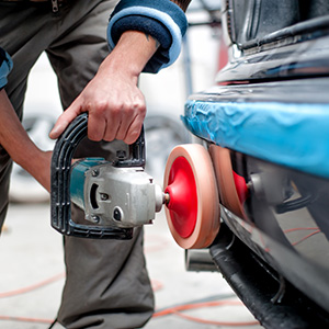 A body shop worker buffing a bumper